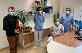 Chefarzt Dr. Rüdiger Hilfenhaus (sitzend) und Personalleitung Berthold Remiger (links) gratulieren Walid Alharithi (rechts) und Samir Ahmed (2.v.l.) zu ihren Ernennungen. Neben Glückwünschen gab es auch ein kleines Willkommensgeschenk.