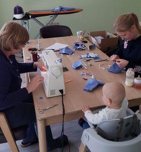 Drei Generationen sitzen beim Maskennähen für die Eichhof-Stiftung an einem Tisch.