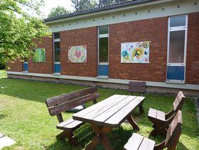 Die drei Tafeln aus dem Projekt Senioren-Graffiti verschönern das Gebäude der Tagesstätte und tragen zur Entspannung im hauseigenen Garten mit Sitzgelegenheit bei.