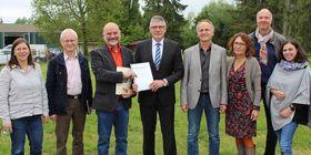 Landrat Manfred Görig übergibt dem Leiter der Vogelsberger Lebensräume, Harry Bernadis, den Bescheid über die jährliche Zuwendung