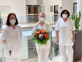 Mit einem Blumenstrauß gratulieren die Bereichsleitungen Andrea Rubenbauer (rechts) und Ramona Eichenauer der neuen Praxisanleiterin Ilona Trabandt zu ihrer gelungenen Fortbildung.