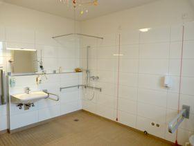 Neben Toiletten und Funktionsräumen steht ein eigenes Bad mit WC und Dusche bereit.