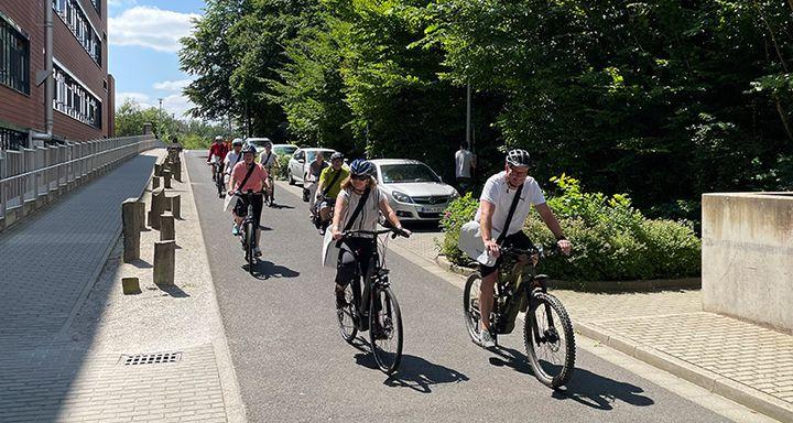 Probefahren mit den neuen E-Bikes. Teilnehmer des Programms beim entspannten Radeln für Gesundheit und Umwelt.